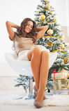Full length portrait of  woman sitting near christmas tree Royalty Free Stock Images