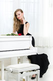 Full-length portrait of woman standing near the piano Royalty Free Stock Image