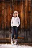 Full length portrait of woman standing near rustic wood wall Stock Photo