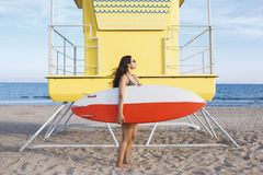 Full length portrait of women holding surfboard with copy space for your brand while standing near lifeguard house on the beach Royalty Free Stock Images