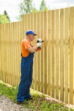 Full-length portrait of worker constructing wooden fence. Full-length portrait of worker dressed in blue overalls  and white gloves constructing wooden fence Stock Photos