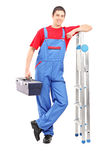 Full length portrait of a worker holding a tool box and leaning. Against ladder on white background stock photography