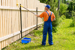 Full-length portrait of worker painting a wooden wall with paint roller. Full-length portrait of painter wearing blue dungarees, orange t-shirt, cap and gloves Royalty Free Stock Images