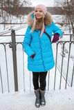 Full length portrait young adorable blond woman wearing blue hooded coat strolling in snowy winter city park bridge. Nature cold s Stock Images