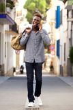 Full length young african male traveler walking outdoors and talking cell phone. Full length portrait of young african male traveler walking outdoors and talking Royalty Free Stock Photo