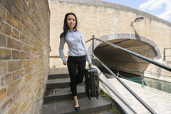 Full length portrait of young asian businesswoman with luggage walking down stairs Stock Photo