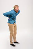 Full length portrait of young bearded man having back pain Royalty Free Stock Image