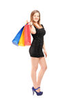 Full length portrait of a young beautiful female carrying shoppi Stock Images