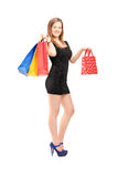 Full length portrait of a young beautiful female carrying shoppi Stock Photos