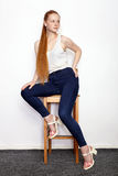 Full length portrait of young beautiful redhead beginner model woman in white t-shirt blue jeans practicing posing showing emotion. Young beautiful redhead stock photo