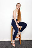 Full length portrait of young beautiful redhead beginner model woman in white t-shirt blue jeans practicing posing showing emotion Stock Image
