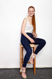 Full length portrait of young beautiful redhead beginner model woman in white t-shirt blue jeans practicing posing showing emotion Royalty Free Stock Image
