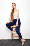 Full length portrait of young beautiful redhead beginner model woman in white t-shirt blue jeans practicing posing showing emotion Royalty Free Stock Images