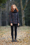 Full length portrait young beautiful redhead woman in scarf and plaid jacket on forest path with autumn foliage background cold se Stock Image