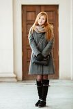 Full length portrait of young beautiful redhead woman wearing coat and scarf posing outdoors with architectural background Stock Image