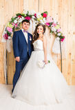 Full length portrait of a young bride and groom posing together. Royalty Free Stock Images