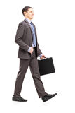 Full length portrait of a young businessman with briefcase walki Royalty Free Stock Image