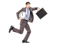 Full length portrait of a young businessman running late. With a clock and a briefcase on white background stock image