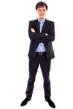 Full length portrait of a young businessman standing with arms f Stock Image