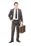 Full length portrait of a young businessman in suit holding a br Royalty Free Stock Images