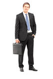 Full length portrait of a young businessman in suit holding a su Stock Images