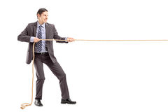Full length portrait of a young businessman in suit pulling a rope stock photography