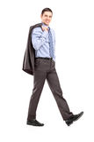 Full length portrait of a young businessman walking with a coat Stock Photo