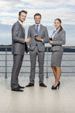 Full length portrait of young businesspeople holding wineglasses on terrace Royalty Free Stock Photo