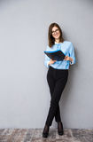 Full length portrait of a young businesswoman with folder Stock Photos