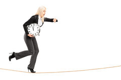 Full length portrait of a young businesswoman running late on a. Rope isolated on white background Royalty Free Stock Images