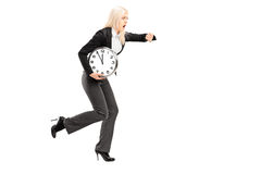 Full length portrait of a young businesswoman running late with Royalty Free Stock Image