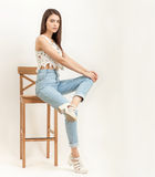 Full length portrait of young calm beautiful brunette woman posing for model tests against white background sitting on bar stool Stock Photography