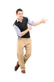 Full length portrait of a young cheerful man pointing Royalty Free Stock Image