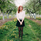 Full length portrait of a young cute redhead woman in a apple garden. Full length portrait of a young cute redhead woman in a apple orchard Stock Image