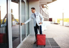 Full length portrait of young executive with a suitcase. Businessman walking to hotel lobby. Full length portrait of young executive with a suitcase Royalty Free Stock Photography