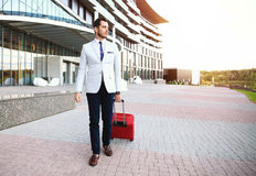 Full length portrait of young executive with a suitcase. Businessman walking to hotel lobby. Full length portrait of young executive with a suitcase Royalty Free Stock Images