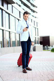 Full length portrait of young executive with a suitcase. Businessman walking to hotel lobby. Full length portrait of young executive with a suitcase Royalty Free Stock Image