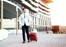 Full length portrait of young executive with a suitcase. Businessman walking to hotel lobby. Full length portrait of young executive with a suitcase Stock Photography