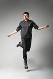 Young fashion male jumping on grey background Royalty Free Stock Images