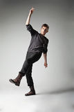 Young fashion male jumping on grey background Stock Images