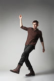 Young fashion male jumping on grey background Royalty Free Stock Photo