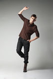 Young fashion male jumping on grey background Stock Photos