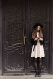 Full length portrait of a young fashionable hipster girl with long brunette hair chatting on her cell telephone Royalty Free Stock Photos