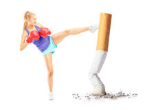 Full length portrait of a young female with boxing gloves kicking with her leg a cigarrette stock photos