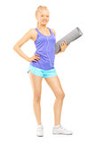 Full length portrait of a young female holding an exercising mat Stock Images