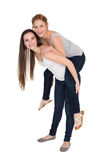 Full length portrait of a young female piggybacking friend Royalty Free Stock Images