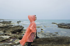 Full length portrait of a young female runner stretching legs muscles before her morning jog near the sea. Fit woman dressed in raincoat do physical exercises on Royalty Free Stock Photo
