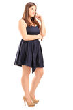 Full length portrait of a young female standing and thinking Royalty Free Stock Photos