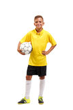A full-length portrait of a young footballer in a yellow T-shirt holes in arms a ball isolated on a white background. Royalty Free Stock Images