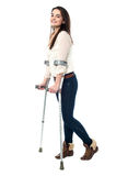 Full length portrait of young girl walking with crutches Royalty Free Stock Photos